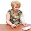 Senior lady measures arterial pressure. — Stock Photo