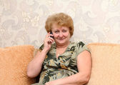 Senior lady speaks by a mobile phone. — Stock Photo