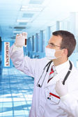 Doctor resarch a medical test glass with blood. — Stock Photo