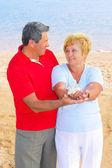 Elderly couple on the coast ,holding corals. — Stock Photo