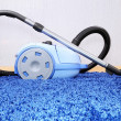 Vacuum cleaner stand  on blue carpet. - ストック写真