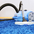 Vacuum cleaner stand  on blue carpet. - Stock Photo
