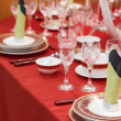 Table appointments on red tablecloth. — Stock Photo