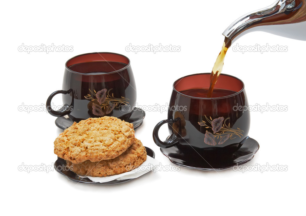 Still life - cookies, two cups and pouring tea. Isolated. — Stock Photo #6596232