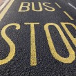 Bus stop sign painted on asphalt road — Stock Photo