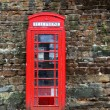 The British red phone booth on old wall - Stock Photo