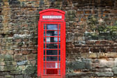 The British red phone booth on old wall — Stock Photo