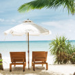 View of two chairs and white umbrella on the beach — Stock Photo