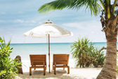 View of two chairs and white umbrella on the beach — Стоковое фото