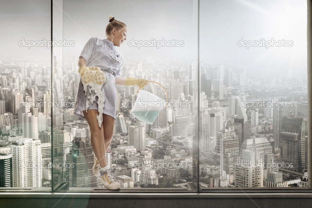 Portrait of young hotel maid  washing glass on the big city background — Stock Photo #5961623