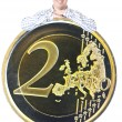Man with big coin 2 euro — Stock Photo #5643233