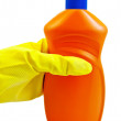 A bottle of orange in yellow-gloved hand in the — Stock Photo