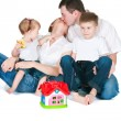 Happy family near a toy small house — Stock Photo