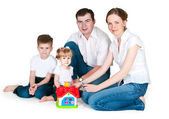 Happy family near a toy small house — Stockfoto