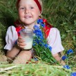 The little girl with a milk glass on hay — Stock Photo