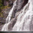 Waterfall on the bank of Lysefjorden in Norway - Stock Photo