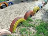 Refused color tyre heap on sand, recycling concept. — Stock Photo