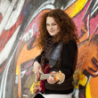 Fashion teen girl with guitar at graffiti background. — Stock Photo