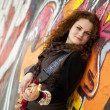 Fashion teen girl with guitar at graffiti background. — Stock Photo #5421603
