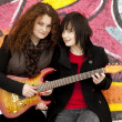 Royalty-Free Stock Photo: Two style teen girls with guitar at graffiti background.