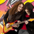 Two style teen girls with guitar at graffiti background. — Stock Photo