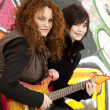 Stock Photo: Two style teen girls with guitar at graffiti background.