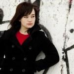 Fashion teen girl at white graffiti background. — Stock Photo