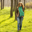 Beautiful red-haired girl walking at green grass at park. — Foto Stock