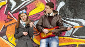 Teen couple with guitar at graffiti background. — Stock Photo