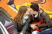Teen couple kissing at graffiti background. — Stock Photo