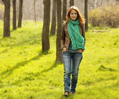 Beautiful red-haired girl walking at green grass at park. — Stock Photo