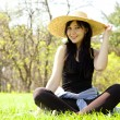 Beautiful brunette girl in hat at the park. - Stock Photo