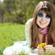 Stock Photo: Beautiful brunette girl in blue glasses at the park.