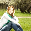 Redhead girl with headphone in the park. — Stock Photo