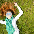 Girl lies at green grass in the park. — Stock Photo