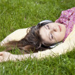 Brunette girl with headphone lies in the park. — Stock Photo #5464446
