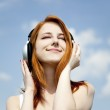 Redhead girl with headphone at sky background. — Stock Photo #5544664