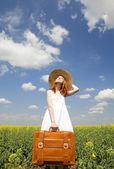 Redhead enchantress with suitcase at spring rapeseed field. — Stock Photo