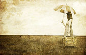 Redhead enchantress with umbrella and suitcase at spring wheat f — Stock Photo