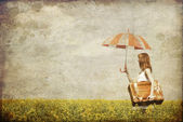 Redhead enchantress with umbrella and suitcase at spring rapesee — Stock Photo