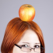Redhead girl keep apple on her head. — Stock Photo #5563822
