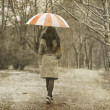 Lonely girl walking at alley in the park in rainy day. — Stock Photo #5563833