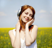 Girl with headphone at rapeseed field. — Stock Photo