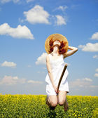 Redhead enchantress fly over spring rapeseed field at broom. — Stock Photo