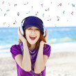 Girl with headphone and notes at the beach. — Stock Photo