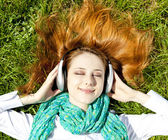 Redhead girl with headphone lies in the park. — Stock Photo