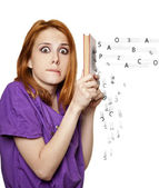 Redhead girl hiding behind a book of flying letters. — Stock Photo