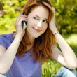 Beautiful redhead girl with mobile phone at the park in summer t — Stock Photo #5745150
