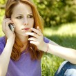 Surprised redhead girl with mobile phone at the park in summer t — Stock Photo #5745162