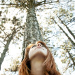 Beautiful redhead girl at the park in summer time looking up. — Stock Photo #5745171